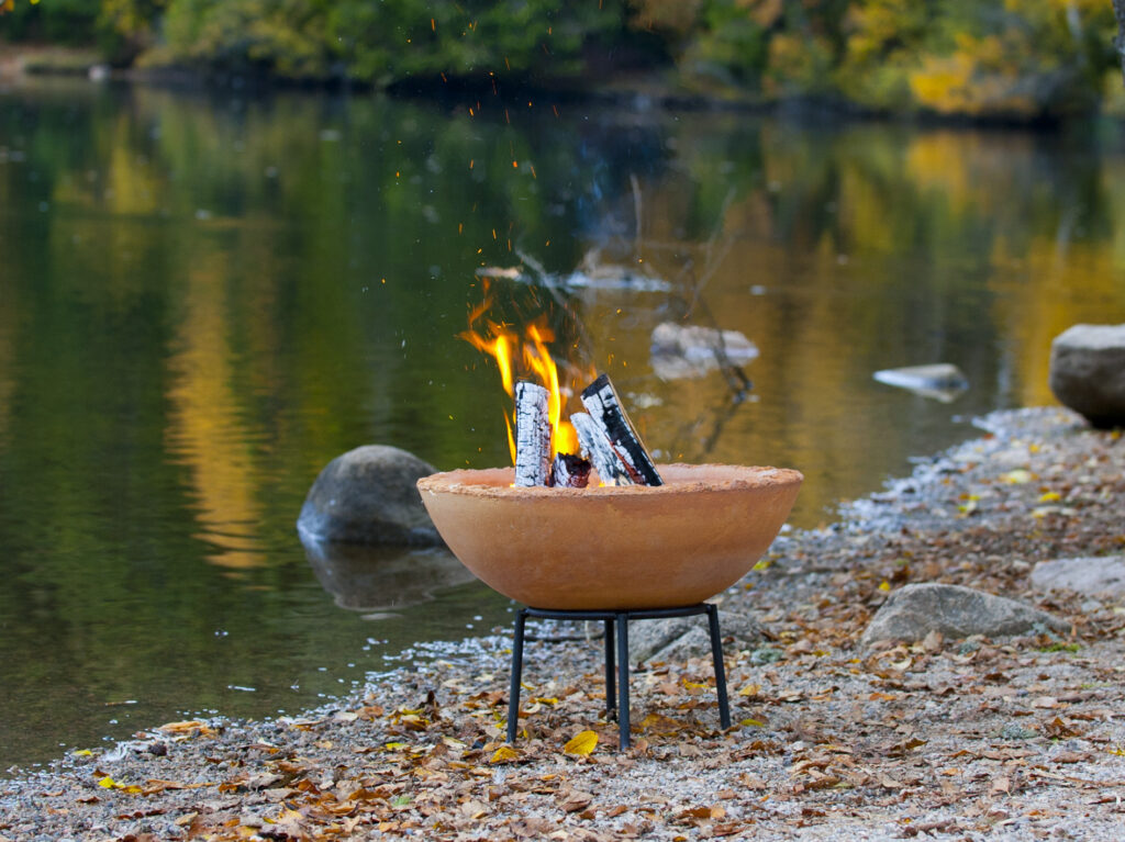 brennende Feuerschale im Kies am Seeufer